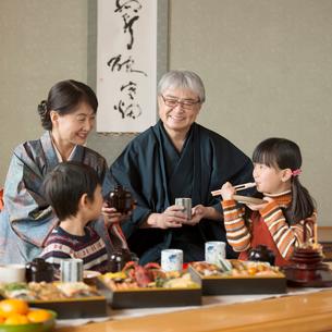 おせち料理を食べる祖父母と孫の写真素材 [FYI01951362]