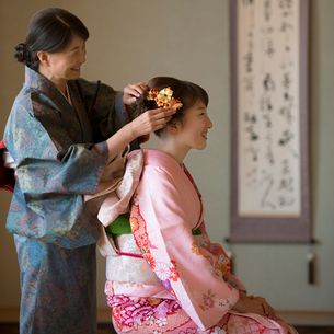 母親に髪飾りをつけてもらう娘の写真素材 [FYI01951427]