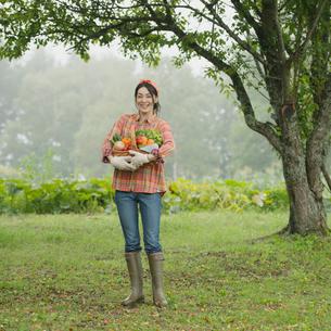 農園で野菜を持ち微笑む女性の写真素材 [FYI01951444]