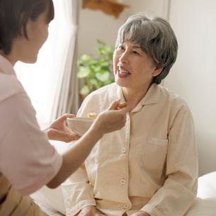 ホームヘルパーにおかゆを食べさせてもらうシニア女性の写真素材 [FYI01951466]