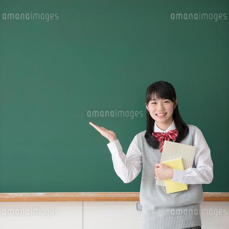 黒板の前で微笑む女子校生の写真素材 [FYI01951495]