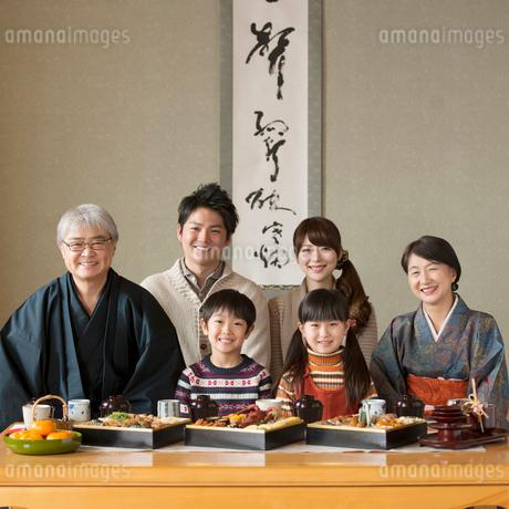テーブルの上に並ぶおせち料理と微笑む3世代家族の写真素材 [FYI01951506]