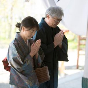 神社でお参りをするシニア夫婦の写真素材 [FYI01951604]