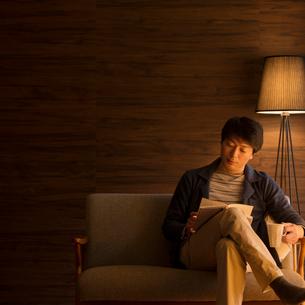ソファーに座り本を読むミドル男性の写真素材 [FYI01951651]