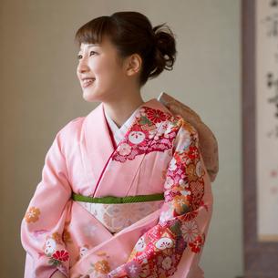 掛け軸の前で微笑む着物姿の女性の写真素材 [FYI01951678]