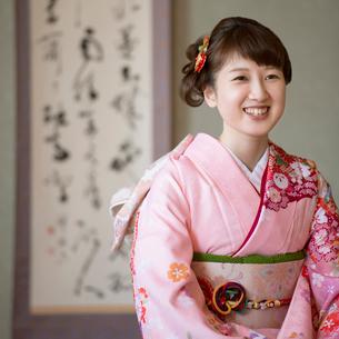 掛け軸の前で微笑む着物姿の女性の写真素材 [FYI01951709]