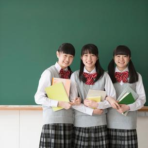 黒板の前で微笑む女子校生の写真素材 [FYI01951760]