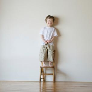 椅子の上に立ち微笑むハーフの男の子の写真素材 [FYI01951763]