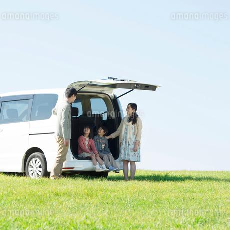 車の荷台に座り談笑をする家族の写真素材 [FYI01951790]