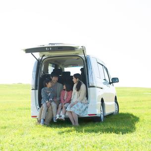 車の荷台に座り談笑をする家族の写真素材 [FYI01951791]