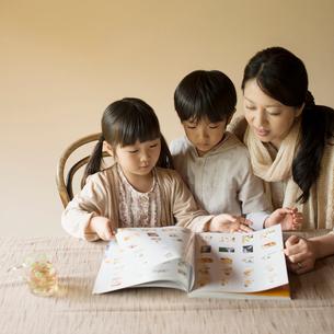 本の読み聞かせをする親子の写真素材 [FYI01951801]