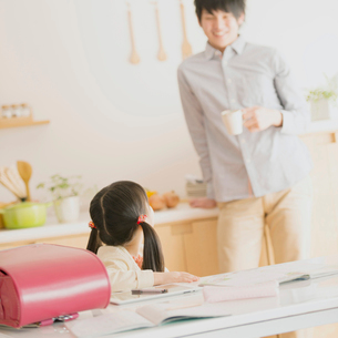 勉強をする女の子と会話をする父親の写真素材 [FYI01951870]