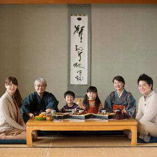 テーブルの上に並ぶおせち料理と微笑む3世代家族の写真素材 [FYI01951874]