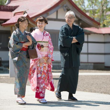 神社の境内を歩く家族の写真素材 [FYI01951877]