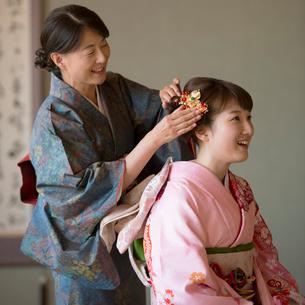 母親に髪飾りをつけてもらう娘の写真素材 [FYI01951902]