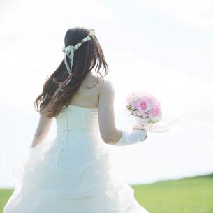 草原でブーケを持つ花嫁の後姿の写真素材 [FYI01951940]