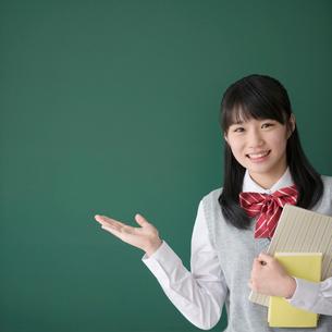 黒板の前で微笑む女子校生の写真素材 [FYI01951941]