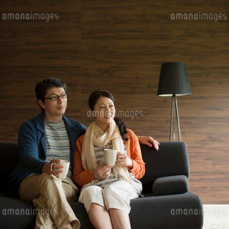 ソファーに座りくつろぐミドル夫婦の写真素材 [FYI01951957]