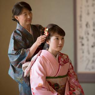 母親に髪飾りをつけてもらう娘の写真素材 [FYI01952000]