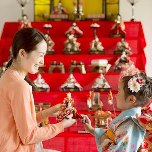 雛人形の飾り付けをする親子の写真素材 [FYI01952009]