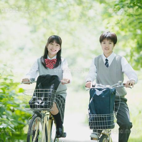 新緑の中で自転車に乗る2人の学生の写真素材 [FYI01952032]