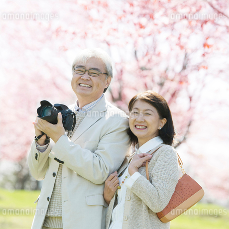 桜の前で微笑むシニア夫婦の写真素材 [FYI01952035]