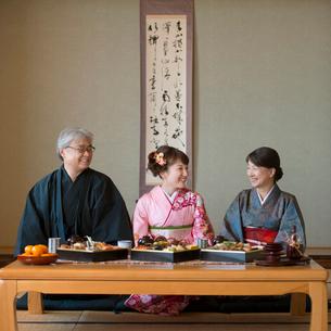 テーブルの上に並ぶおせち料理と微笑む家族の写真素材 [FYI01952062]