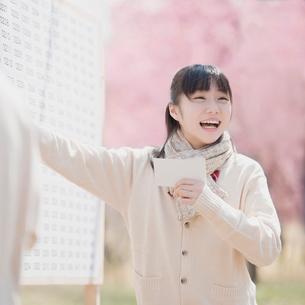 合格発表のボードを見て喜ぶ女子中学生の写真素材 [FYI01952101]