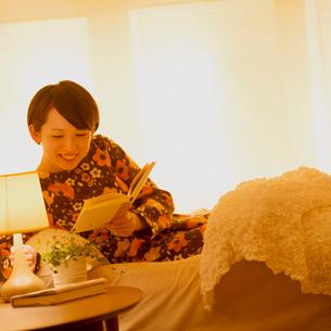 ベッドで本を持ちライトを消す女性の写真素材 [FYI01952126]