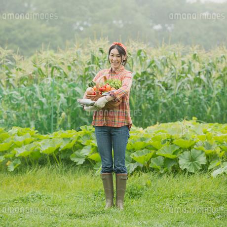 農園で野菜を持ち微笑む女性の写真素材 [FYI01952153]