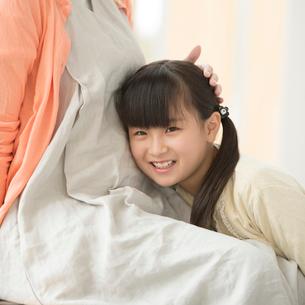 母親のお腹に耳をあてる女の子の写真素材 [FYI01952155]