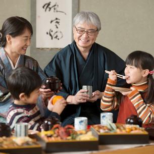 おせち料理を食べる祖父母と孫の写真素材 [FYI01952172]
