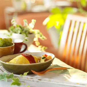 テーブルの上のオムライスと観葉植物の写真素材 [FYI01952214]