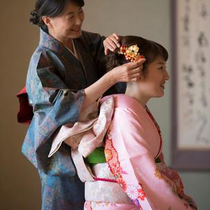 母親に髪飾りをつけてもらう娘の写真素材 [FYI01952233]
