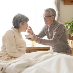 妻におかゆを食べさせる夫の写真素材 [FYI01952302]