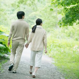 公園を散歩するミドル夫婦の後姿の写真素材 [FYI01952319]