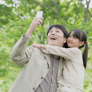 スマートフォンで写真を撮る親子の写真素材 [FYI01952339]
