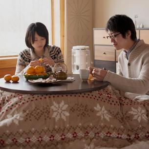 こたつでミカンを食べるカップルの写真素材 [FYI01952376]