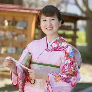 神社でおみくじを持ち微笑む女性の写真素材 [FYI01952384]