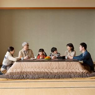 こたつで談笑をする3世代家族の写真素材 [FYI01952425]