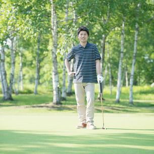 ゴルフクラブを持ち微笑む男性の写真素材 [FYI01952431]