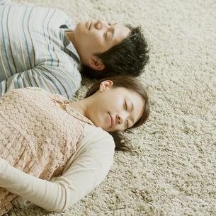 カーペットの上で眠るカップルの写真素材 [FYI01952489]