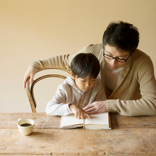 本の読み聞かせをする親子の写真素材 [FYI01952528]