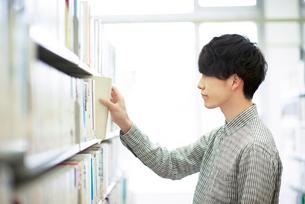 図書館で本を選ぶ男性の写真素材 [FYI01952545]