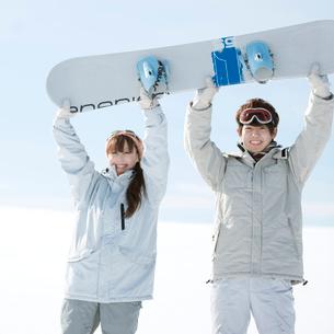 スノーボードを持ち微笑むカップルの写真素材 [FYI01952564]