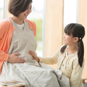 母親のお腹に手をあてる女の子の写真素材 [FYI01952624]
