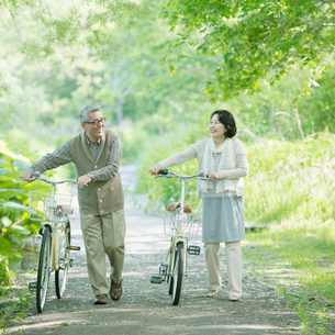 自転車を押すシニア夫婦の写真素材 [FYI01952673]