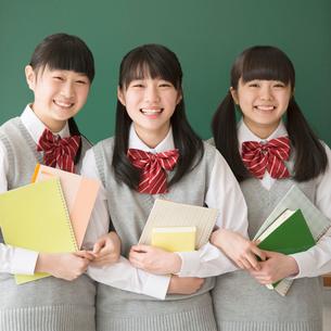 黒板の前で微笑む女子校生の写真素材 [FYI01952703]