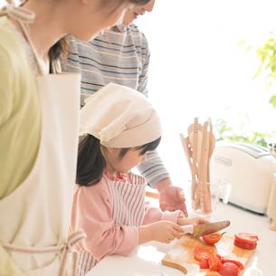 キッチンでお手伝いをする女の子と両親の写真素材 [FYI01952705]