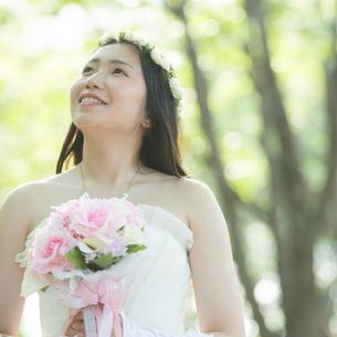 森林の中でブーケを持ち微笑む花嫁の写真素材 [FYI01952744]
